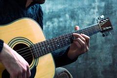 弹在一个混凝土墙的背景的年轻人一把声学吉他 免版税库存图片
