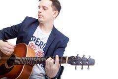 弹在一台蓝色起重器的一个年轻人的特写镜头一把声学吉他 免版税库存照片