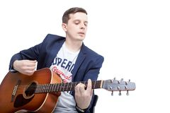弹在一台蓝色起重器的一个年轻人的特写镜头一把声学吉他 免版税图库摄影