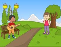 弹在公园动画片的孩子吉他 免版税库存照片