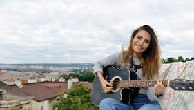 弹在公园的背景的女孩吉他 图库摄影