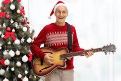 弹在圣诞节前面的愉快的前辈一把声学吉他 免版税图库摄影