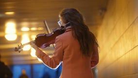 弹在地铁的桃红色外套的Talanted年轻女人小提琴 影视素材