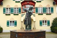 弹在城镇厅前面的年轻莫扎特雕塑小提琴 村庄Sankt Gilgen,奥地利 免版税库存照片