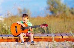 弹在夏天领域的逗人喜爱的男孩一把吉他 免版税库存照片