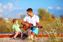 弹在夏天领域的逗人喜爱的男孩和一个人画象一把吉他 免版税图库摄影