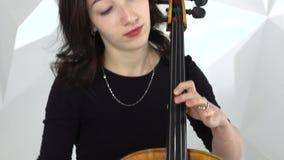 弹在大提琴的两个女孩小提琴一在白色演播室 影视素材