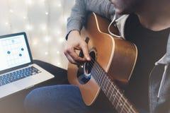 弹在家庭环境,人的行家吉他学习在乐器,在膝上型计算机的笔记在背景焕发bokeh Christm 图库摄影