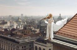 弹在屋顶的边缘的上面的妇女小提琴 免版税库存图片
