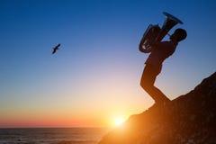 弹在岩石沿海的一个年轻人的剪影喇叭在惊人的日落期间 免版税库存图片
