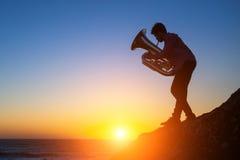 弹在岩石沿海的一个年轻人的剪影喇叭在日落期间 免版税库存照片