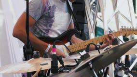 弹在摇滚乐队的吉他弹奏者一把电吉他在聚焦回到背景的生活表现期间 ? 影视素材