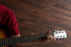弹在木背景的人的手六串吉他 音乐会海报的模板 库存照片