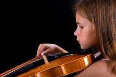 弹在桃红色礼服的女孩小提琴 免版税库存图片