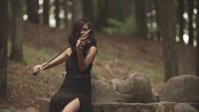 弹在森林年轻小提琴手的礼服的女孩小提琴使用与启发 股票视频