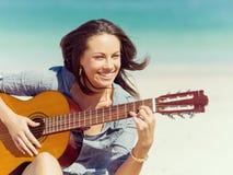 弹在海滩的美丽的少妇吉他 免版税库存图片