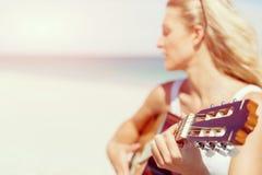 弹在海滩的美丽的少妇吉他 图库摄影