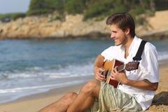 弹在海滩的英俊的人经典吉他 库存照片