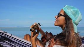 弹在海滩的逗人喜爱的白种人年轻行家女孩尤克里里琴吉他 慢动作的HD 酸值phangan泰国 影视素材