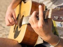 弹在海滩的年轻人一把声学吉他 库存图片