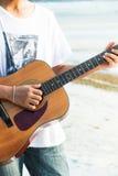 弹在海滩的年轻人吉他 免版税图库摄影
