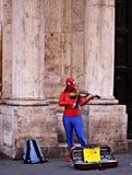 弹在罗马街道的超级英雄小提琴  免版税库存图片