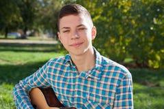 弹在自然的少年吉他 免版税库存图片