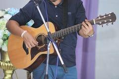 弹在舞台背景的亚裔音乐家声学吉他 免版税库存图片