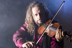 弹在蓝色烟的英俊的人古典小提琴 免版税库存图片