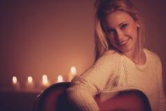 弹在蜡烛光的年轻白肤金发的妇女吉他 免版税库存图片