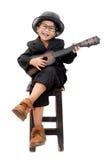 弹在被隔绝的白色背景的亚裔男孩吉他 免版税库存图片