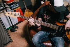 弹在车库顶视图的低音吉他弹奏者吉他 库存照片