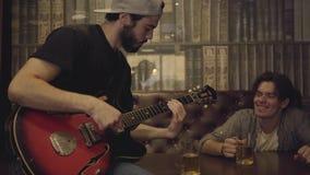 弹在酒吧,他的朋友的年轻有胡子的人吉他坐在摇他的在节奏的头附近 在客栈的休闲 股票录像