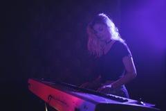 弹在阶段的女性音乐家钢琴在夜总会 免版税库存照片
