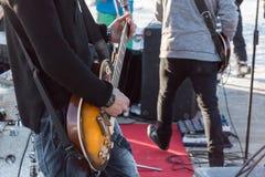 弹在音乐会的吉他弹奏者电子吉他 免版税库存照片