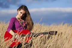 弹在领域的国家女孩一把声学吉他反对蓝色多云天空背景 免版税库存照片