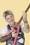 弹在黄色背景的愉快的资深男性庞克摇滚乐音乐家画象吉他 库存照片
