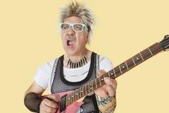 弹在黄色背景的资深男性低劣的音乐家吉他 图库摄影