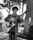弹声学吉他的年轻人在公园 库存照片