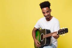 弹声学吉他的年轻英俊的非裔美国人的减速火箭的被称呼的吉他弹奏者隔绝在金银铜合金背景 免版税库存照片