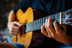 弹声学吉他的年轻音乐家 库存照片