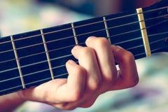 弹声学吉他的年轻音乐家 免版税库存照片