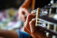 弹声学吉他的年轻音乐家 免版税图库摄影