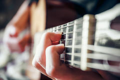 弹声学吉他的年轻音乐家 免版税库存图片