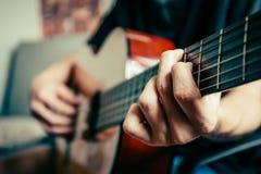 弹声学吉他的年轻音乐家 库存图片