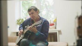 弹声学吉他的男性音乐家 演奏声学吉他慢动作录影的人 在屋子里坐长沙发 人 影视素材