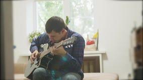 弹声学吉他的男性音乐家 演奏声学吉他慢动作录影的人 在屋子里坐长沙发 影视素材
