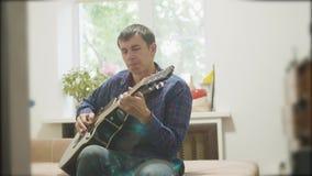 弹声学吉他的男性音乐家 演奏声学吉他慢动作录影的人 在屋子里坐长沙发 股票录像