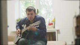 弹声学吉他的男性音乐家 演奏声学吉他慢动作录影的人 在屋子里生活方式坐 股票视频