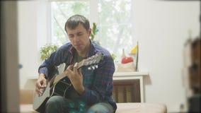 弹声学吉他的男性音乐家 演奏声学吉他慢动作录影的人 在生活方式屋子坐 股票视频